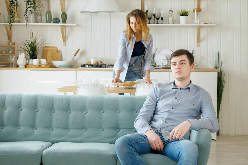 Den nätta frun lägger tabellmaken sitter på hållande ögonen på TV för soffan royaltyfri bild