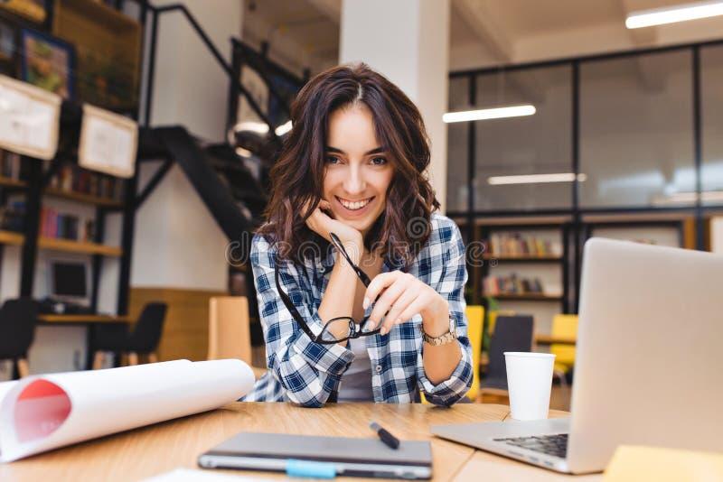 Den nätta glade unga kvinnan som sitter på tabellen, omger arbetsmaterial Le till kameran, planlägga som arbetar som freelancer royaltyfri bild