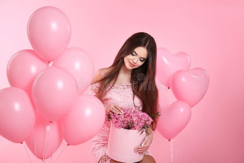 Den nätta gulliga brunettflickan med ballonger och buketten av rosen flödar arkivfoto