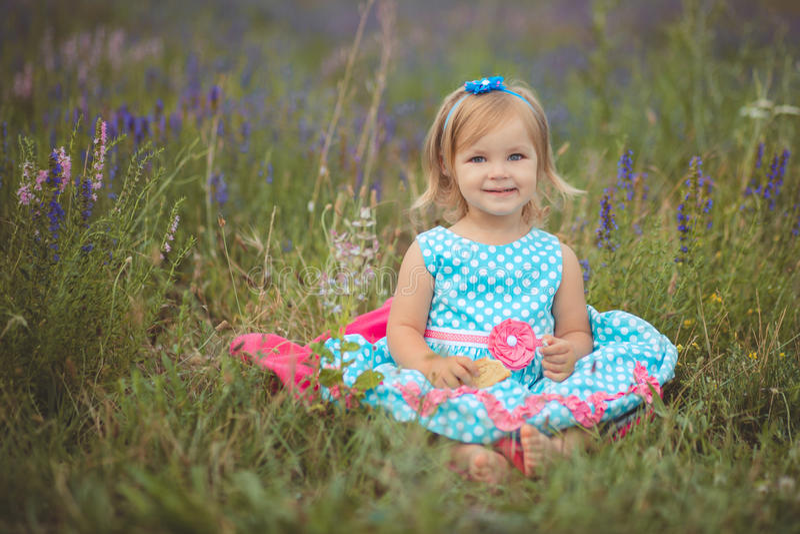 Den nätta gulliga lilla flickan bär den vita klänningen i ett lavendelfält som rymmer en korg full av purpurfärgade blommor royaltyfri foto