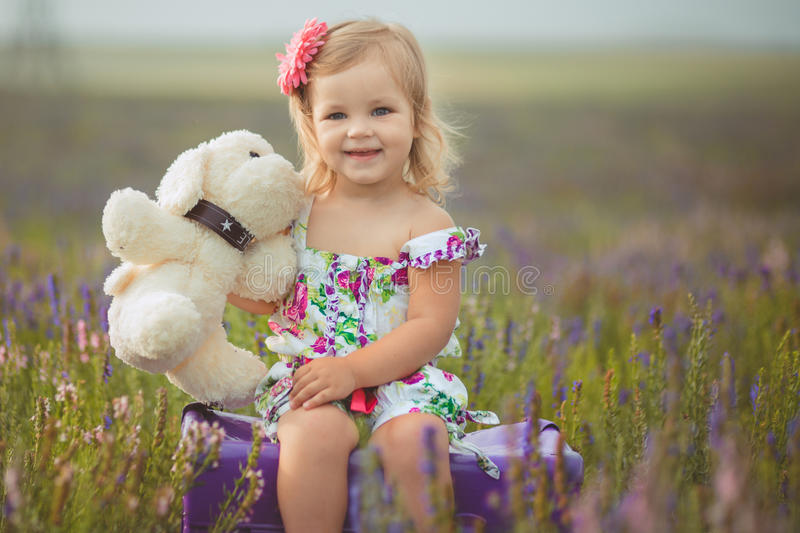 Den nätta gulliga lilla flickan bär den vita klänningen i ett lavendelfält som rymmer en korg full av purpurfärgade blommor royaltyfria foton