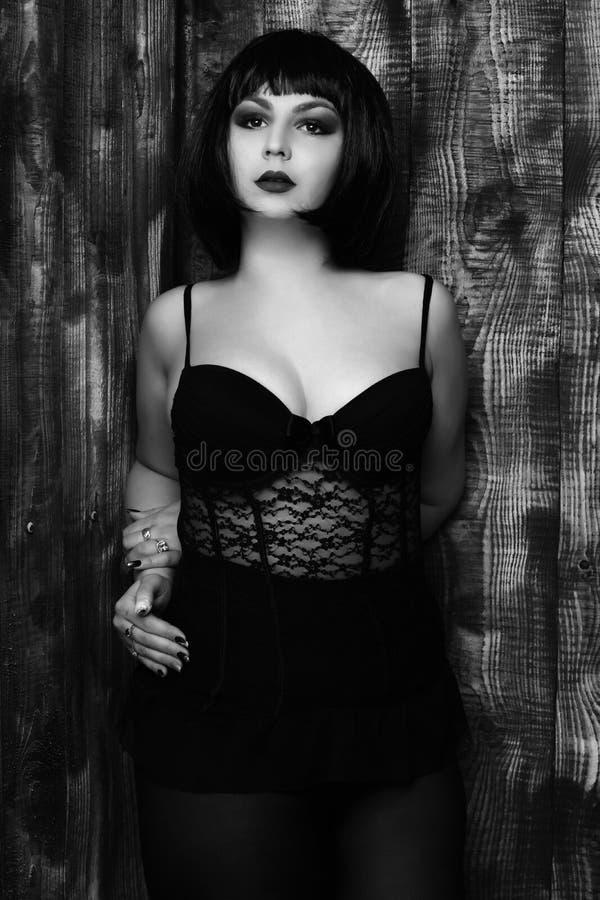 Den nätta gulliga unga stilfulla brunettkvinnan i sexigt snör åt korsetten eller underkläderna på fyllig kropp i svart peruk med  royaltyfri foto