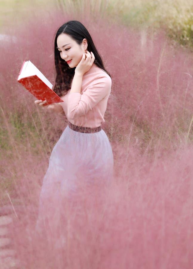 Den nätta härliga gulliga asiatiska kinesiska kvinnaflickaläseboken i ett blommafält som är utomhus- i sommarhöstnedgång, parkera royaltyfri fotografi