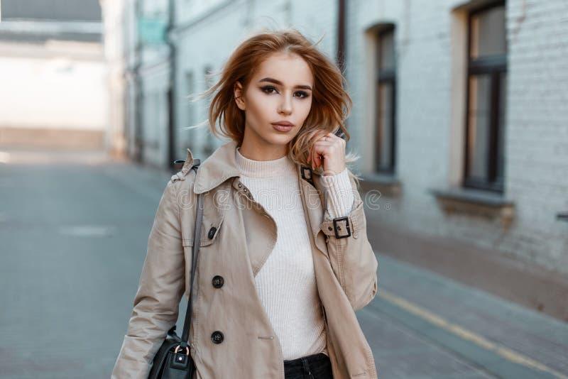 Den nätta härliga unga kvinnan i ett stilfullt vårlag i en vit T-tröja med en svart läderpåse går runt om staden arkivfoto