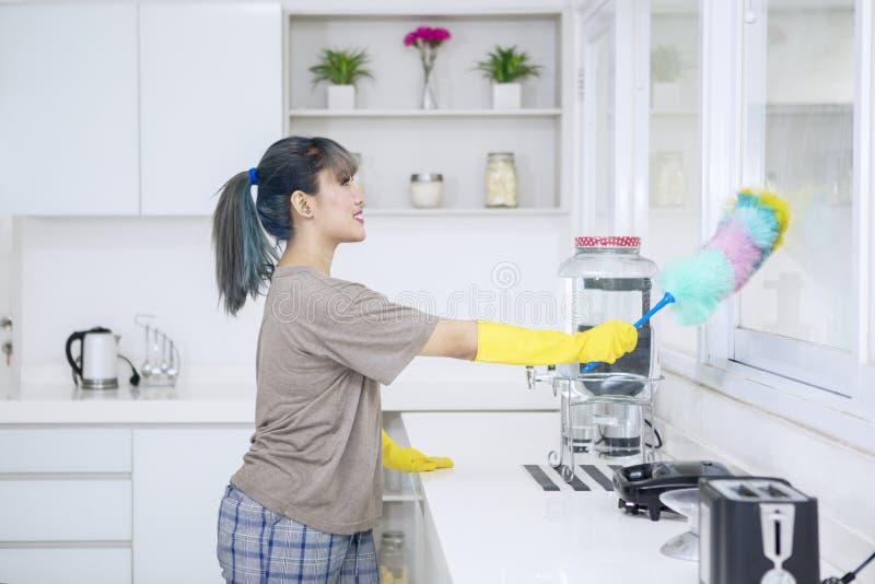 Den nätta hemmafrun gör ren fönster i kök royaltyfri foto