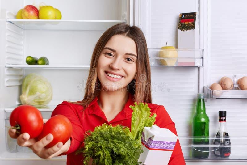Den nätta hemmafrun med förtjust blick visar att produkter vilket hon köpte i specerihandlare` s shoppa Den härliga le kvinnan ry royaltyfri fotografi