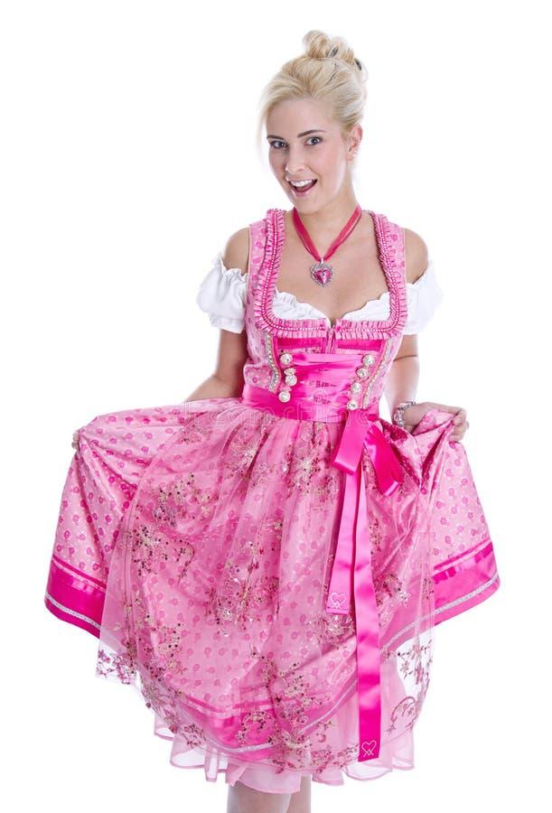 Den nätta isolerade bärande bavarianklänningen för den unga kvinnan kallade dirndlen royaltyfri bild
