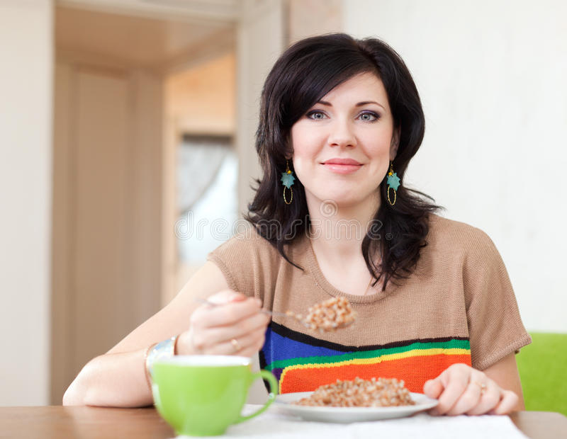 Den nätta kvinnan äter sädesslag hemma arkivfoton