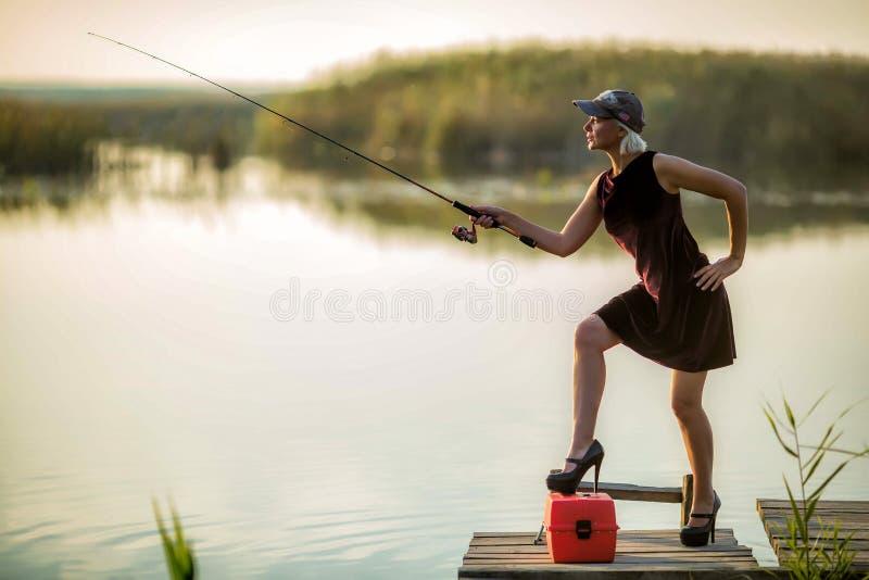 Den nätta kvinnan i en burgundy klänning och svarta skor och en baseballmössa fångar fisken på en träpir royaltyfri foto
