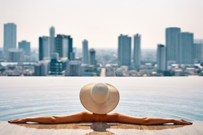 Den nätta kvinnan i hatt kopplar av i simbassäng på taköverkant tycker om cityscapepanoramasikt royaltyfria bilder