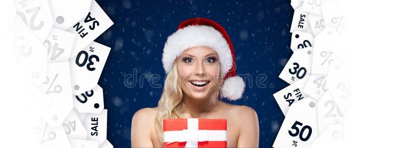 Den nätta kvinnan i jullock räcker objektet av dagen royaltyfri fotografi