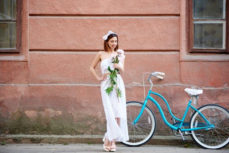 Den nätta kvinnan i den vita klänningen som poserar med blommor och blått, cyklar framme av den gamla röda väggen royaltyfri foto