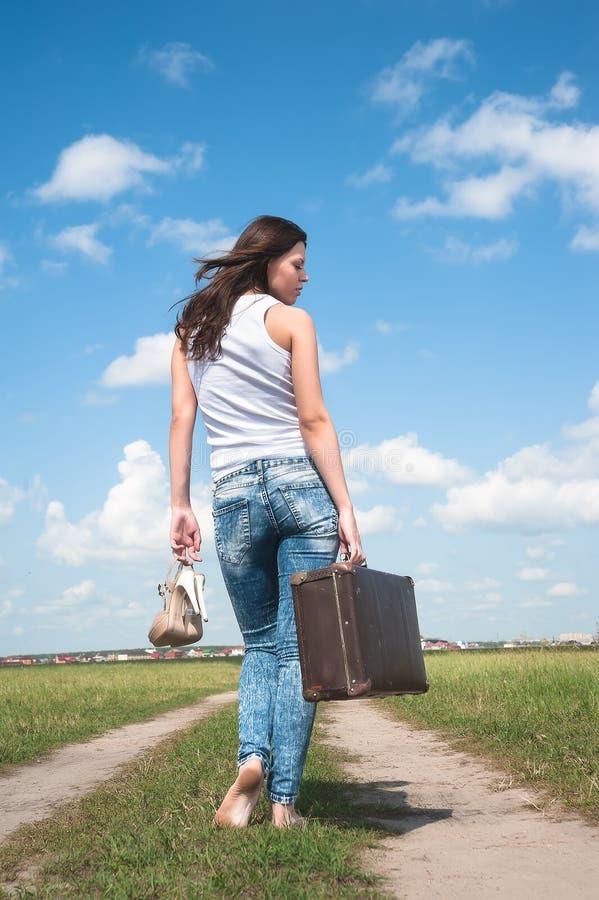 Den nätta kvinnan med den gamla resväskan går avlägsen royaltyfri bild