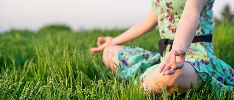 Den nätta kvinnan mediterar i parkera royaltyfri bild