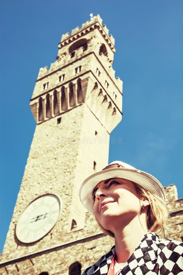 Den nätta kvinnan poserar under Palazzoen Vecchio i Florence royaltyfria bilder