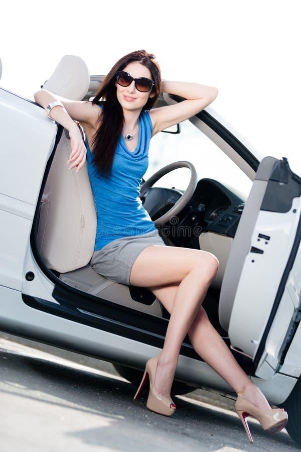 Den nätta kvinnan sitter i den vita bilen med den öppnade sidodörren royaltyfria bilder