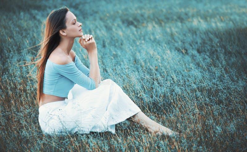 den nätta kvinnan sitter på ett gräs arkivbild