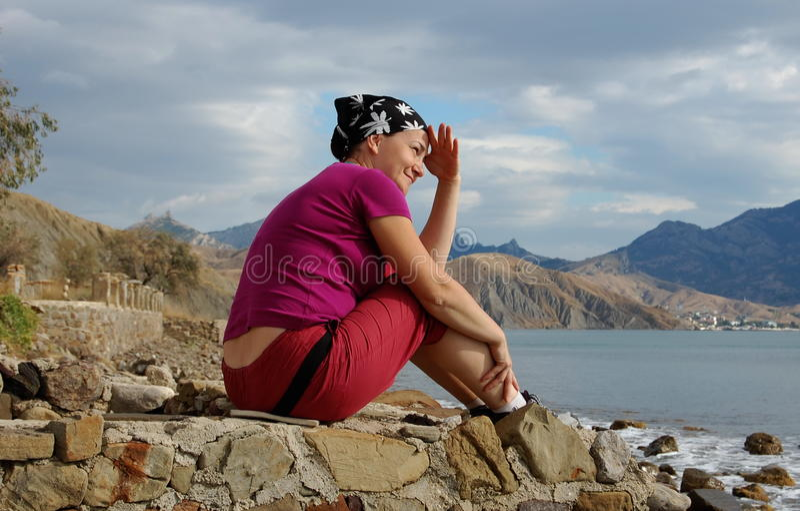 Den nätta kvinnan sitter på kusten och ser avlägsen fotografering för bildbyråer