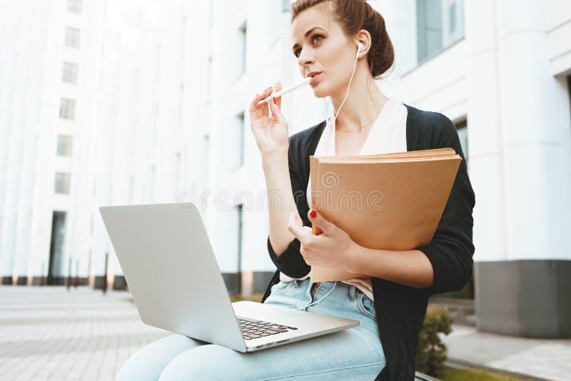 Den nätta kvinnan skriver med pennan på pappers- dokument och information om sökande i internet på bärbara datorn i affärsområde royaltyfria foton