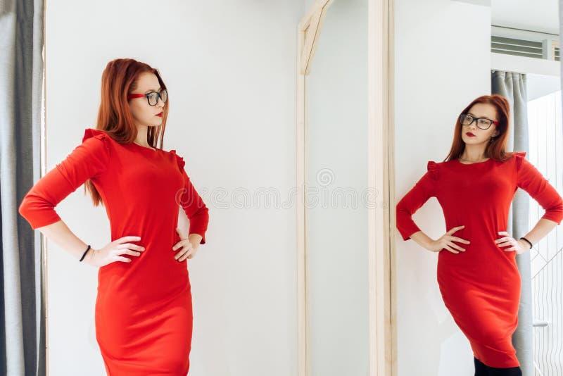Den nätta kvinnan som försöker på kläder i ett passande, shoppar damen i den röda klänningen reflekteras i spegeln royaltyfri bild