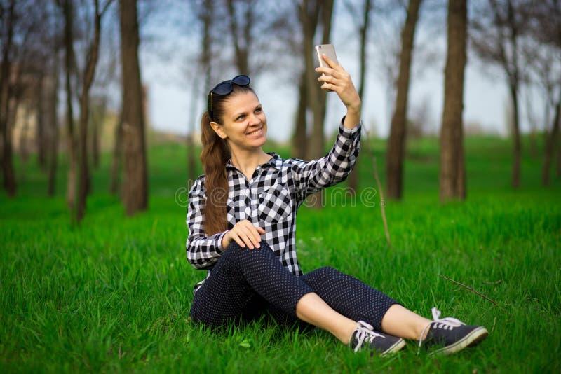 Den nätta kvinnan som in vilar, parkerar och tar selfie på telefonen royaltyfri fotografi