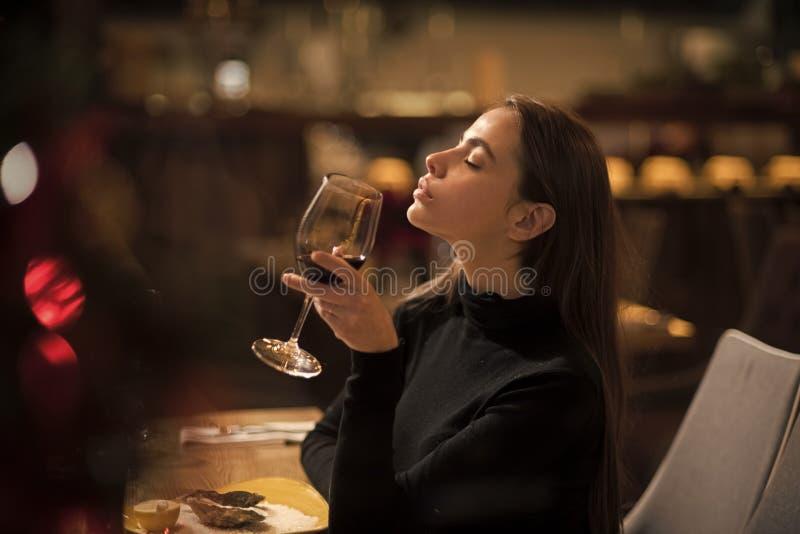 Den nätta kvinnan vilar i restaurang med vinglaset Perfekt vin stångkunden sitter i kafé som dricker alkohol Flicka med länge fotografering för bildbyråer