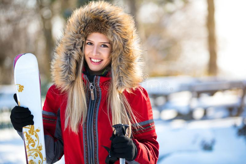 Den nätta kvinnaskidåkaren med skidar och poler royaltyfri foto