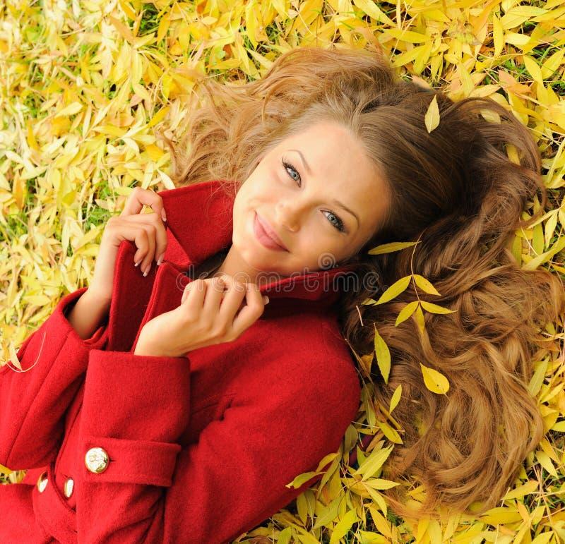Den nätta kvinnaståenden som ligger på gula lönnlöv parkerar in arkivbild