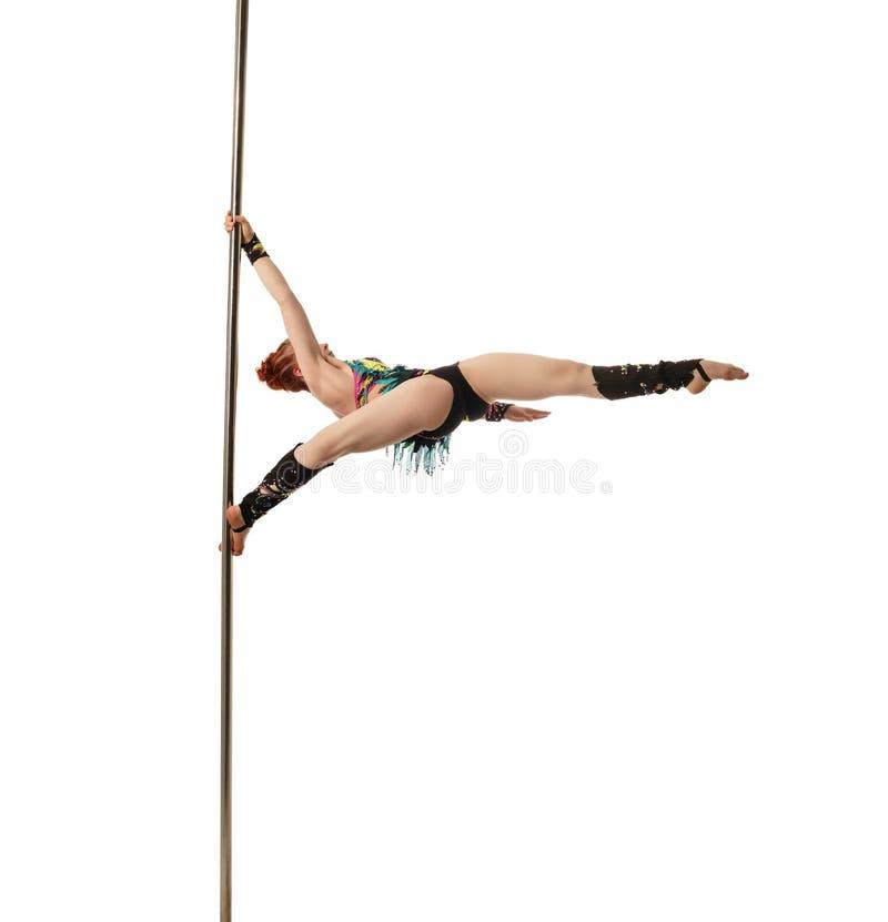 Den nätta kvinnliga gymnasten utför trick på pylonen arkivbild