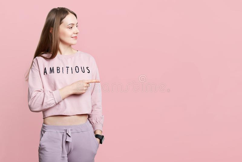 Den nätta kvinnlign har den sportiga kroppen, bär tillfällig kläder, indikerar på tomt kopieringsutrymme åt sidan, poserar mot ro arkivbild