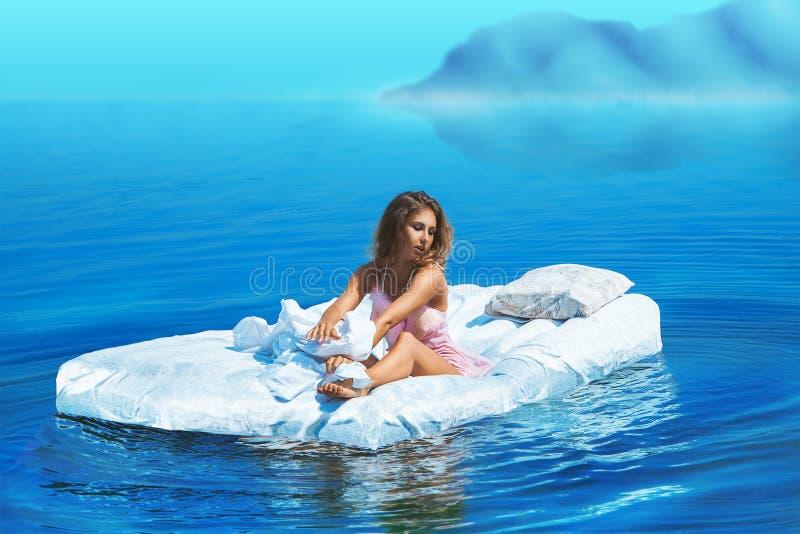 Den nätta kvinnlign sitter på säng i sjön arkivbild
