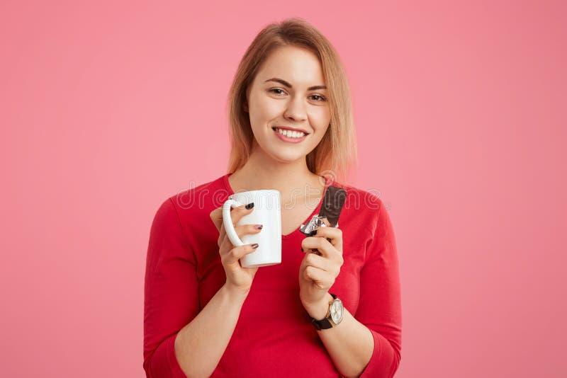 Den nätta kvinnlign, som har gottegrisen, tycker om stången av choklad med koppen kaffe eller te, har lunch- eller kaffeavbrottet arkivbilder