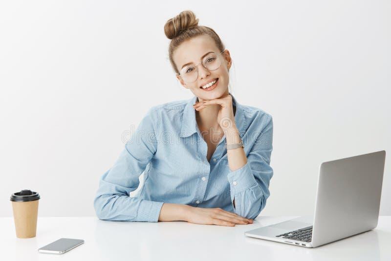 Den nätta le kvinnliga frilans- avlägsna arbetaren bär exponeringsglas genom att använda bärbara datorn som dricker kaffe som kon royaltyfri fotografi