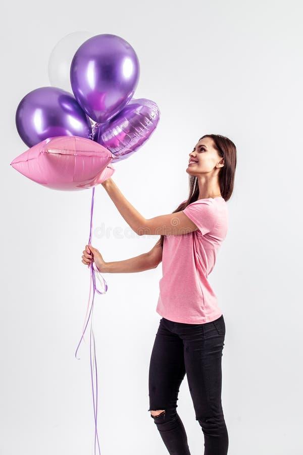 Den nätta le t-skjortan och jeans för flicka iklädda rosa rymmer ballonger i hennes händer på den vita bakgrunden i studion royaltyfria foton