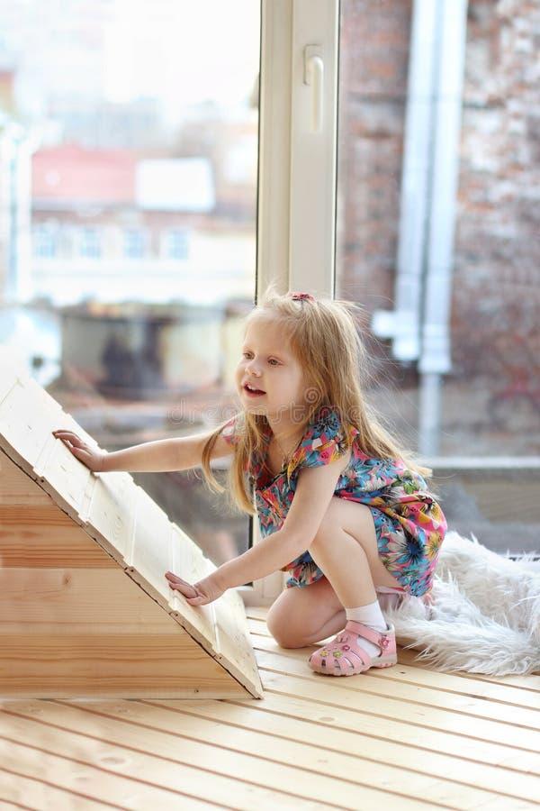 Den nätta lilla blonda flickan squats nära stort fönster royaltyfria foton