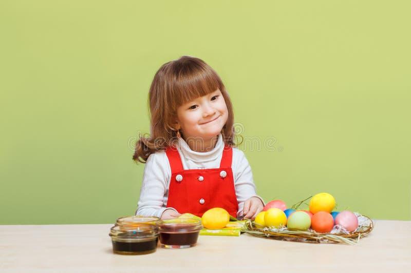Den nätta lilla flickan målar ägg royaltyfri foto