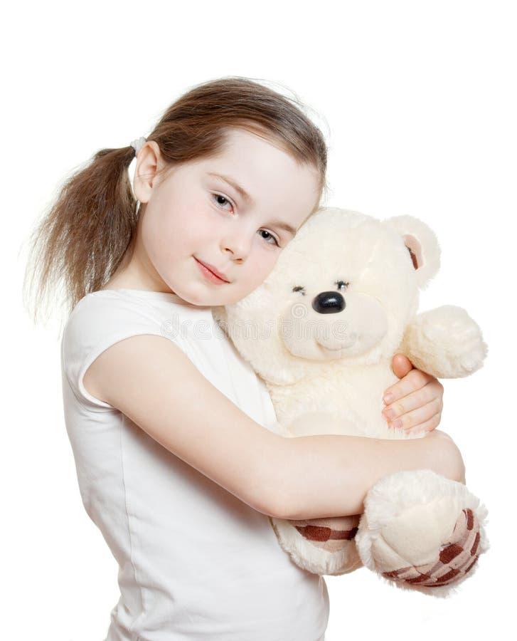 Den nätta lilla flickan omfamnar en nallebjörn arkivbild