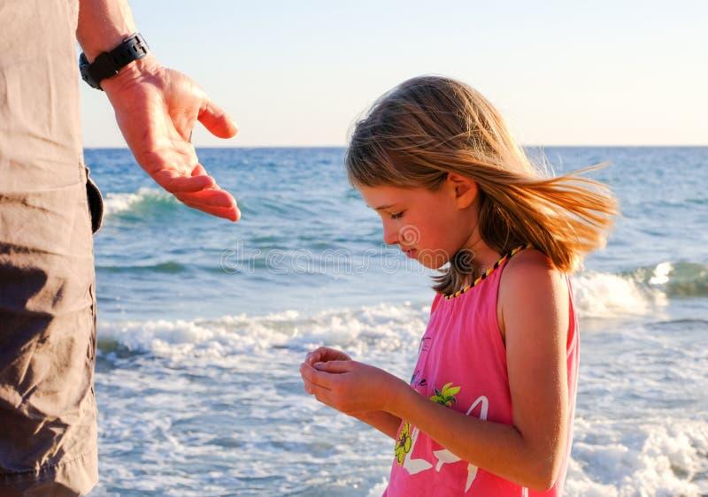 Den nätta lilla flickan rymmer smething i hennes händer och undersöker den royaltyfri bild