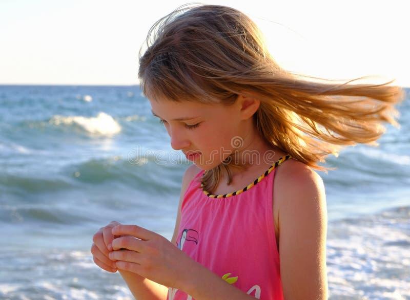Den nätta lilla flickan rymmer smething i hennes händer och undersöker den arkivfoto