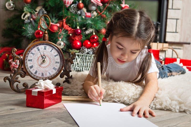 Den nätta lilla flickan skrivar brevet till jultomten nära julträd arkivbilder