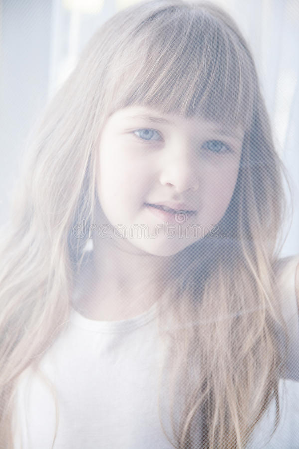 Den nätta lilla flickan som ser till och med en gardin, snör åt royaltyfri foto