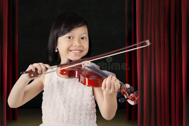 Den nätta lilla flickan spelar fiolen på etappen royaltyfria foton