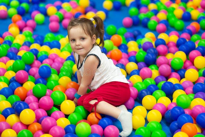 Den nätta lilla flickan spelar i barnzon i munterhetgalleria, ligger på färgglade bollar, ler positivt, ser kameran Liten ch royaltyfria foton