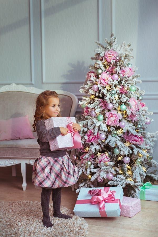 Den nätta lilla flickan står med en gåvaask på händer nära julgranen och ser för att sid royaltyfri foto