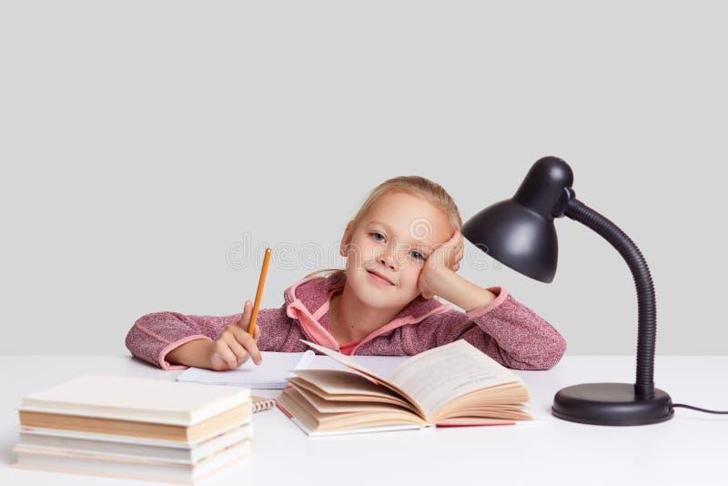 Den nätta lilla ungen har endast utmärkta fläckar, materiella studier, lutar på handen, sitter nära den öppnade boken, har inspir arkivfoton