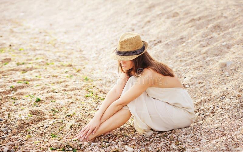 Den nätta lugna kvinnan kopplar av att sitta bara på en sandstrand royaltyfri foto