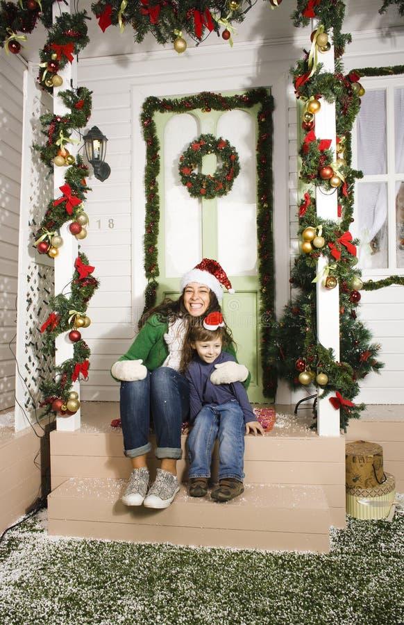 Den nätta lyckliga familjen som sitter av dörr, dekorerade framme på jul arkivfoto