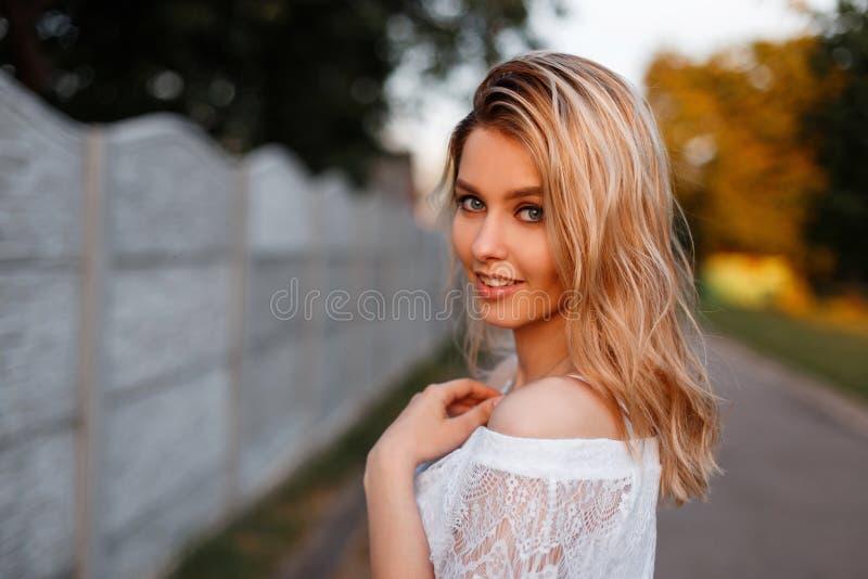 Den nätta lyckliga unga härliga blonda kvinnan i en elegant vit snör åt blusen som utomhus poserar på en solig vårdag gullig flic arkivbild
