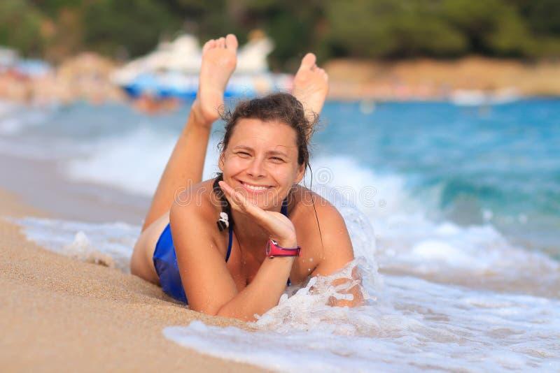 Den nätta lyckliga unga kvinnan ligger på den sandiga havsstranden Le flickan på havet Sommar vilar på stranden Havssemester arkivbilder