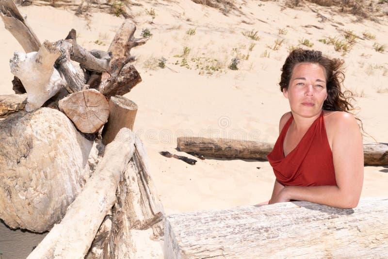 Den nätta mitt åldrades kvinnan på en tropisk strand med trädrivved royaltyfria foton